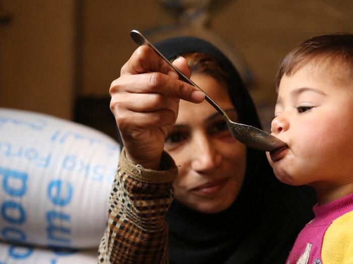 مادر سوریه ای به کودک خود غذا می دهد